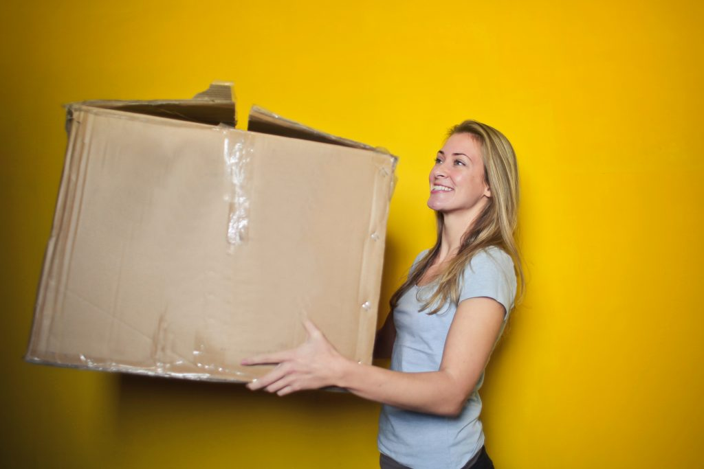 a girl holding a large cardboard box in the storage Virginia
