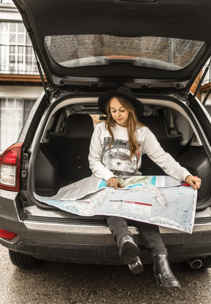 A girl sitting in the open trunk of a car holding a map, preparing to move with movers Howard County MD