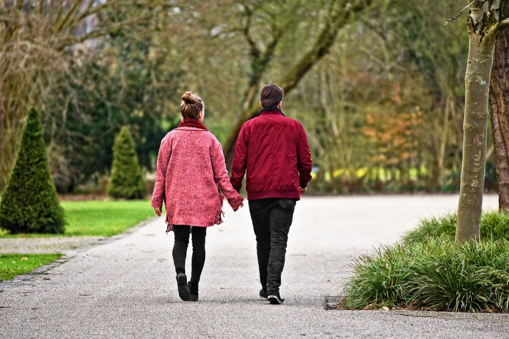 A man and a woman holding hands while strolling through a park