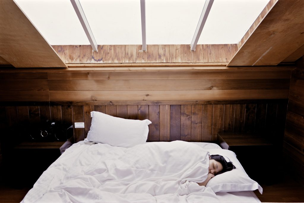 A woman sleeping on a bed, a window above her head