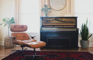 Upright piano and a brown chair, kilim