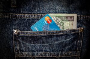 A back jeans pocket with a 100 dollar bill and a Mastercard sticking out