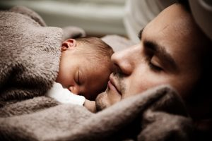 Dad sleeps with a very small baby