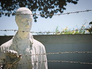 White statue posed to look through a barbed wire