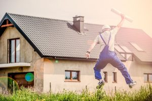 A man dresses as a physical worker jumping for joy in front of a house