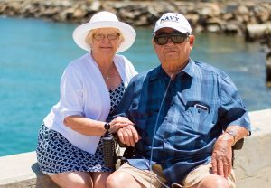 Two elderly people - a man and a woman - holding hands.