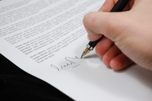 Person signing a storage rental agreement.