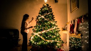 a woman decorating a tree