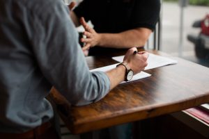 two person writing on paper on brown wooden table