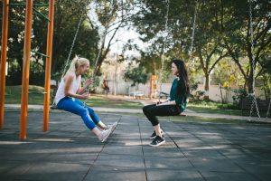 two girls sitting on swing