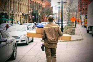 man in brown jacket beside car