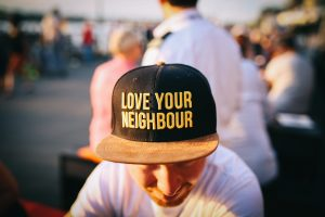 man wearing black cap with love your neighbour print