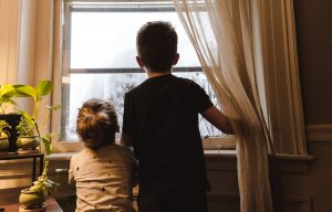 two children looking through the window