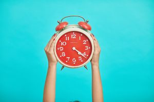 person holding white and red clock