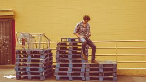man sitting on pallets