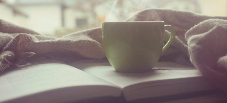 a cup of coffee on a book next to a blanket