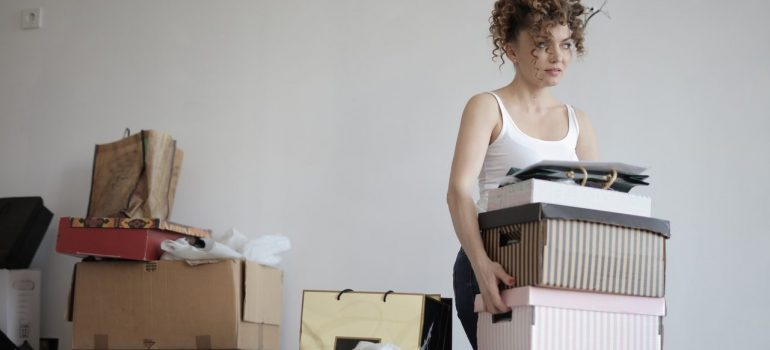 a woman carrying a couple of boxes out of the room