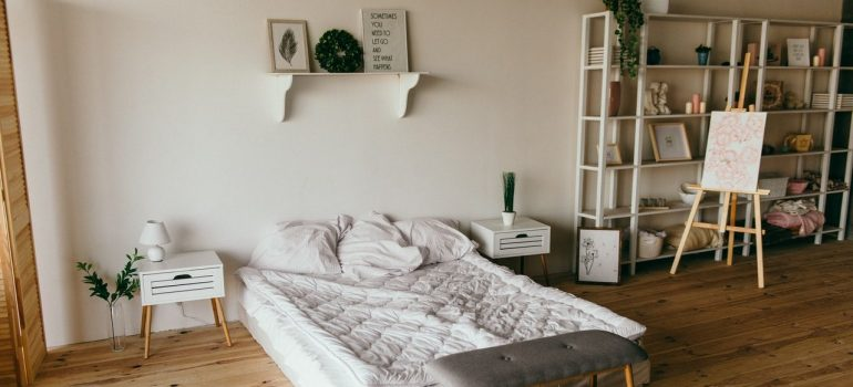 a picture of a minimalist bedroom with a bed and bookshelves near