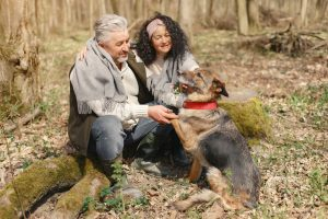a senior couple enjoying their time out in the nature with a dog