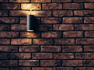 a black lamp on a dark brick wall