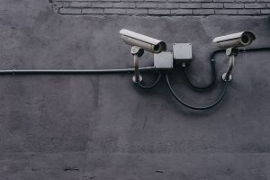 two security cameras on a black wall facing east