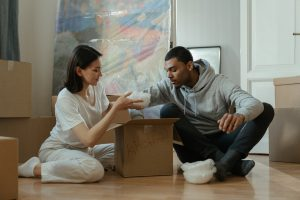 a man and a woman sitting on the floor while unpacking according to their unpacking order