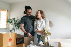 a couple having a laugh as they unpack clothes