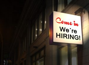 a sign that says we are hiring as a part of find a new job before or after you move guide