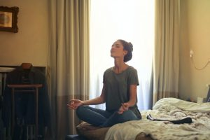 a woman meditating on her bed in the bedroom