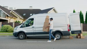 a man carrying boxes from his van to a certain destination as one of the examples of additional moving companies' charges