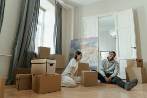 a couple sitting on the floor laughing amongst cardboard boxes after thinking about what to do in the first week of moving to Columbia MD