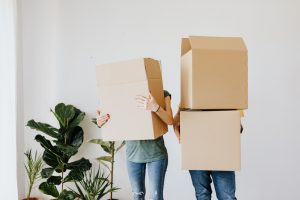 a couple holding cardboard boxes in a light room