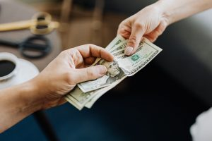 two people exchanging money in a living room