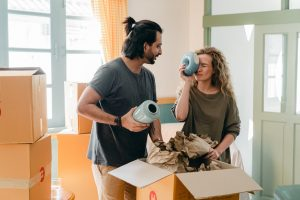a couple having fun with ceramics items as they unpack