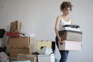 A woman decluttering as a part of Self storage maintenance tips
