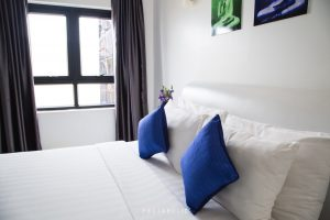 A bed with blue pillows
