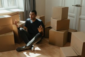 a man meditating in-between boxes to mentally prepare for an interstate move