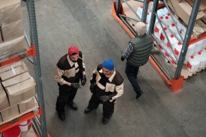 two men talking as one passes by them inside a storage unit
