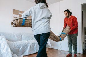 Man and woman lifting a carpet