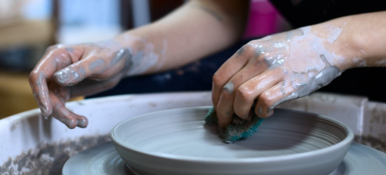 Hands are modeling a plate during pottery class