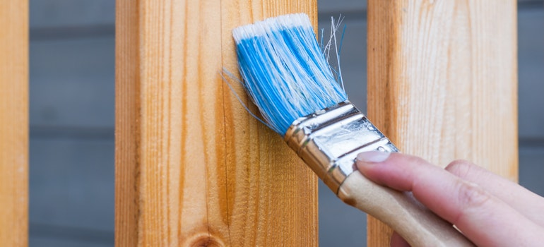 A hand is painting fence with a brush