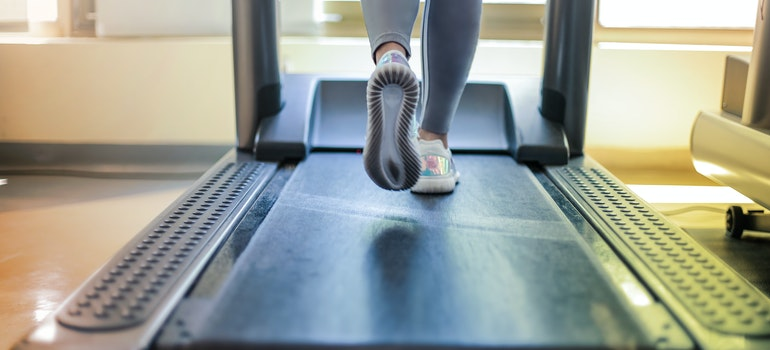 A woman is walking on a treadmill.