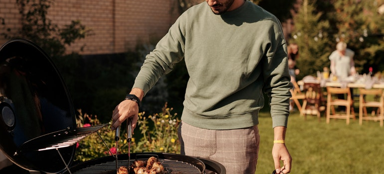 A man is grilling sausages on a BBQ.