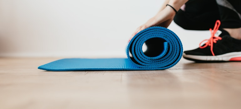 A woman is rolling up a yoga mat.