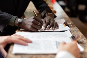A man is signing a document.