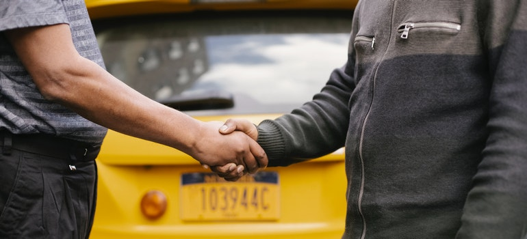 Two men are shaking hands in front of a car.