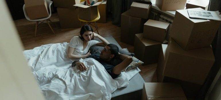A couple laying on a mattress surrounded by boxes