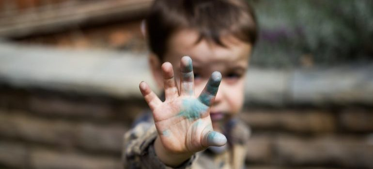 child waving with a dirty hand