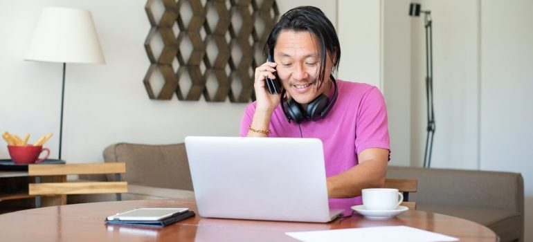 A man on the phone while looking at his laptop