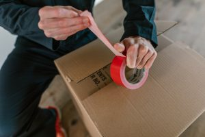 a mover putting a tape on the moving box